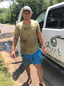 Greer Gardens Landscaping employee Dylan Kemper in dirty work clothes next to Greer Gardens truck Daphne Alabama
